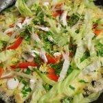 Auf die Eiermasse in der Pfanne sind geschnittenes Gemüse, Pilze und Salat verteilt