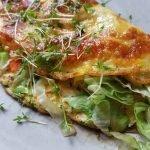Nahaufnahme eines zusammengeklappten Omelettes mit Kresse bestreut und Gemüsefüllung