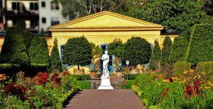 Weg führ auf einen gelben grichischen Tempel zu. Links und rechts Blumenrabatten