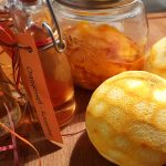 Orangensirup in kleinem Fläschchen, Orangen-Essenz im Glas, geschälte Orange