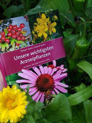Eine Hand hält das Heilpflanzen-Buch zwischen Ringelblume und Paprika
