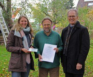 Drei Personen halten Naturgarten Plakette und Urkunde