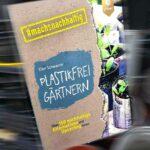 Buchcover vor Gartenplastik-Hintergrund